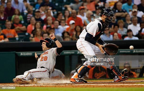 Steve Pearce of the Baltimore Orioles slides safe into home plate in the fourth inning as Jason Castro of the Houston Astros waits for the ball...