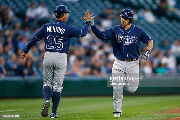 Steve Pearce of the Tampa Bay Rays is congratulated by third base coach Charlie Montoyo after hitting a home run against the Seattle Mariners in the...