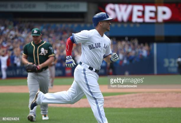 Steve Pearce of the Toronto Blue Jays circles the bases after hitting a grand slam home run in the tenth inning during MLB game action as Liam...