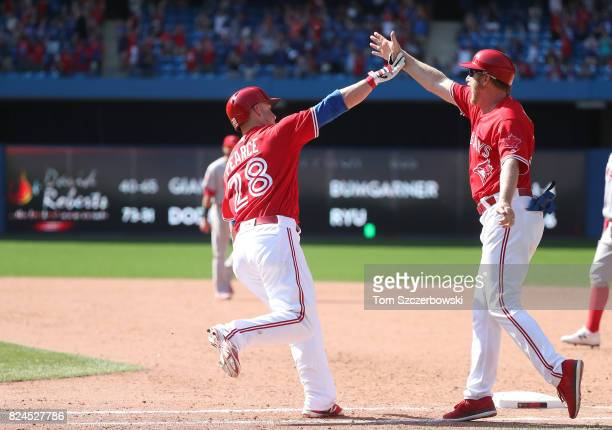 Steve Pearce of the Toronto Blue Jays is congratulated by first base coach Tim Leiper after hitting a gamewinning grand slam home run in the ninth...