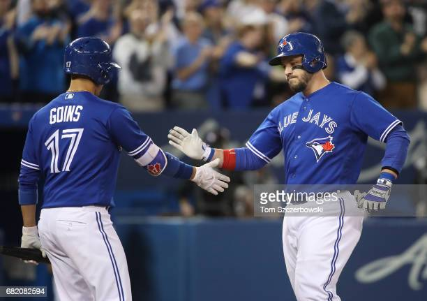 Steve Pearce of the Toronto Blue Jays is congratulated by Ryan Goins after hitting a threerun home run in the fifth inning during MLB game action...