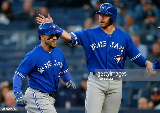 Steve Pearce of the Toronto Blue Jays is congratulated by teammate Justin Smoak after Pearce's threerun home run in the first inning against the New...