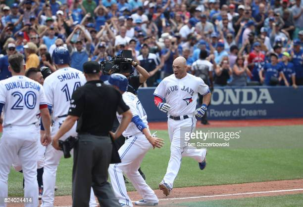 Steve Pearce of the Toronto Blue Jays is greeted at home plate by teammates after hitting a gamewinning grand slam home run in the tenth inning...