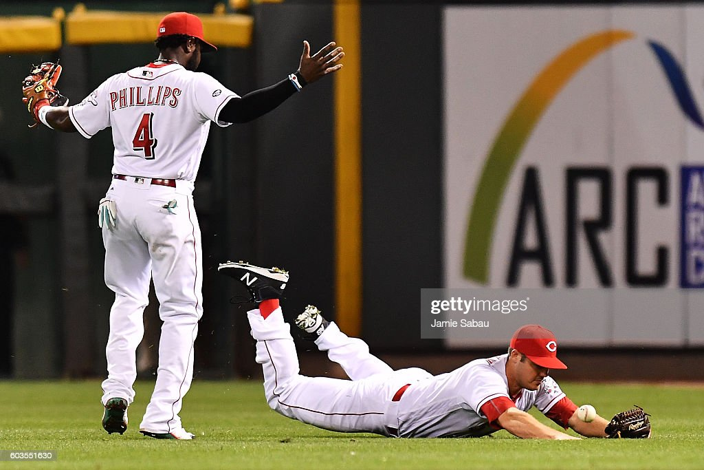 Steve Selsky #51 of the Cincinnati Reds misses a fly ball after making a diving attempt in the seventh inning against the Milwaukee Brewers as Brandon Phillips #4 of the Cincinnati Reds moves in at Great American Ball Park on September 12, 2016 in Cincinnati, Ohio. Cincinnati defeated Milwaukee 3-0.