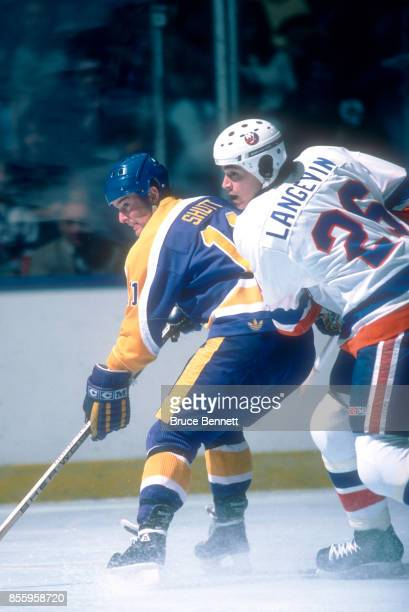 Steve Shutt of the Los Angeles Kings skates on the ice as he is defended by Dave Langevin of the New York Islanders during an NHL game on March 19...