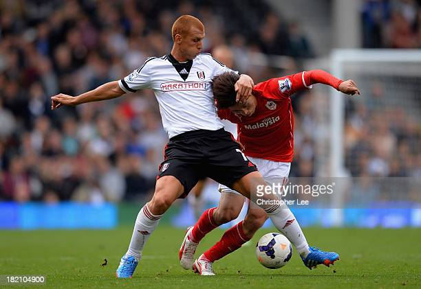 Steve Sidwell of Fulham battles with BoKyung Kim of Cardiff during the Barclays Premier League match between Fulham and Cardiff City at Craven...
