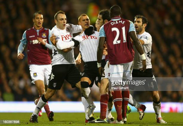 Steve Sidwell of Fulham is held back by team mate Dimitar Berbatov as he argues with Mohamed Diame of West Ham United during the Barclays Premier...