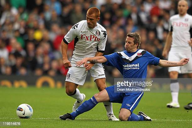 Steve Sidwell of Fulham is tackled by David Magowan of Crusaders during the UEFA Europa League 2nd Qualifying Round 2nd Leg match between Fulham and...