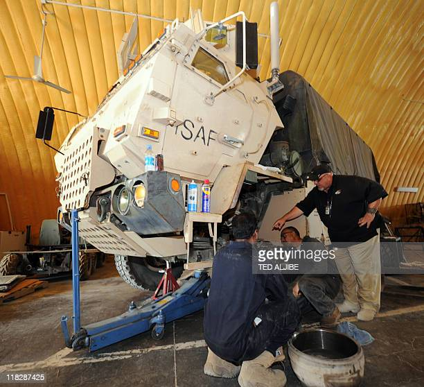 Steve Slashinski of AC First company supervises employees repairing an armoured vehicle at their workshop in Camp Clark in Mandozai district Khost...