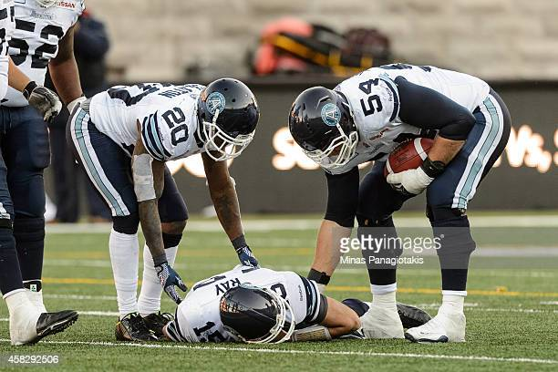 Steve Slaton and Chris Van Zeyl checks on teammate Ricky Ray of the Toronto Argonauts during the CFL game against the Montreal Alouettes at Percival...
