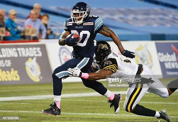 Steve Slaton of the Toronto Argonauts breaks a tackle by Simoni Lawrence of the Hamilton TigerCats to cross the goal line for a touchdown during...