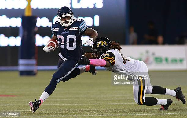 Steve Slaton of the Toronto Argonauts runs the ball as he slips a tackle by Taylor Reed of the Hamilton TigerCats during their game at Rogers Centre...