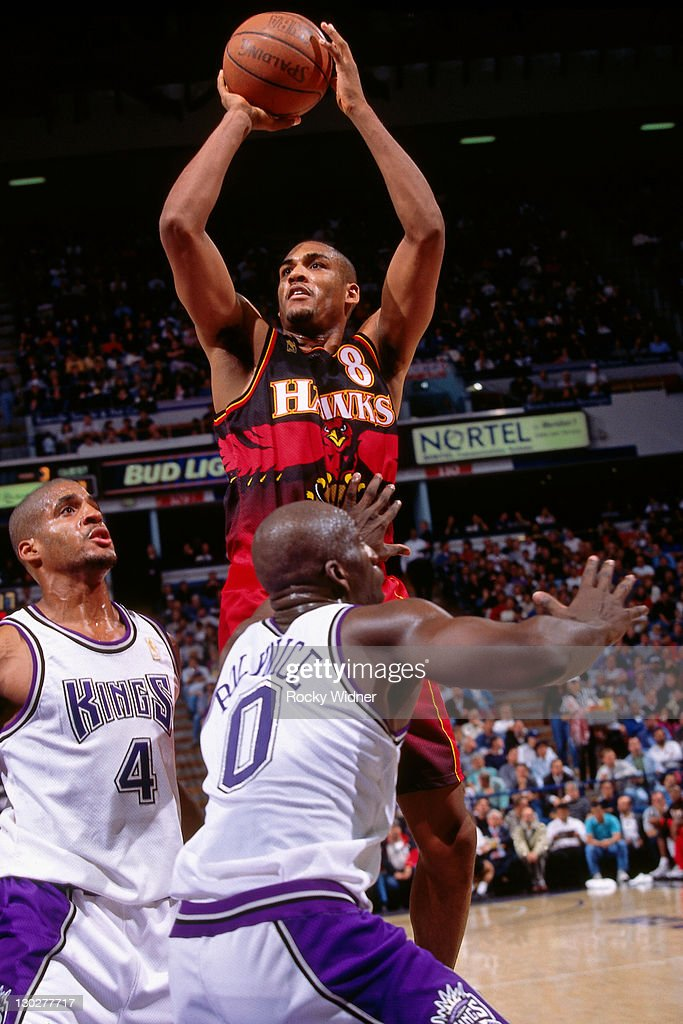 Steve Smith of the Atlanta Hawks shoots against Olden Polynice and Corliss Williamson of the Sacramento Kings on November 7 1996 at Arco Arena in...