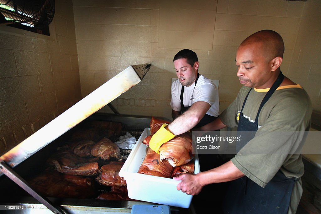 Steve Spoon (L) and Reggie Stuckey remove pork from a smoker at Bill Spoon's Barbecue on July 12, 2012 in Charlotte, North Carolina. The nearly fifty-year-old restaurant, founded by Steve's grandfather, is known for its Eastern North Carolina Style BBQ served with homemade vinegar based BBQ sauce, mustard based coleslaw, and made-from-scratch hushpuppies. The restaurant was recently recognized as one of the ten best BBQ restaurants in the United States. Businesses in Charlotte are anticipating a boost in sales when an estimated 35,000 visitors arrive in the city for the 2012 Democratic National Convention (DNC) September 3-6.