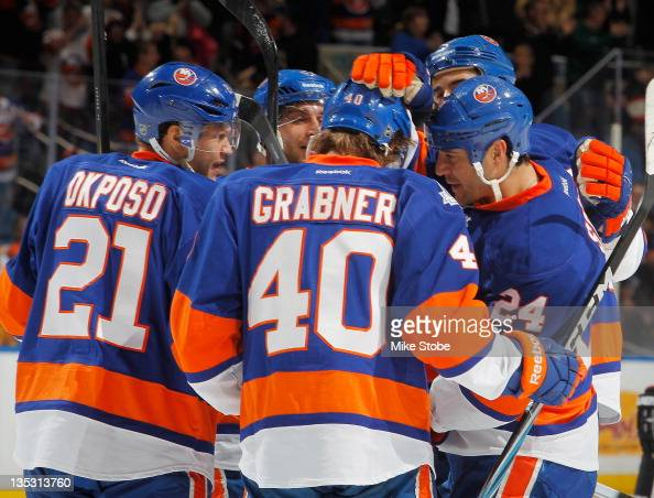 Steve Staios of the New York Islanders celebrates his third period goal with teammates Kyle Okposo and Michael Grabner in a game against the Chicago...