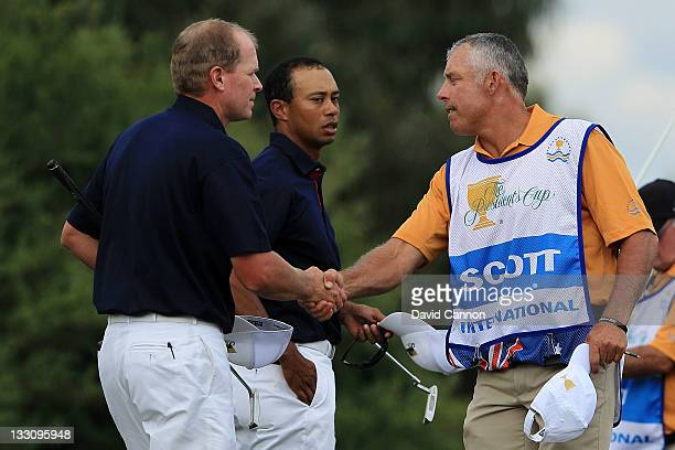 Steve Stricker of the US Team shakes hands with caddie Steve Williams on the 12th hole as Tiger Woods of the US Team looks on during the Day One...