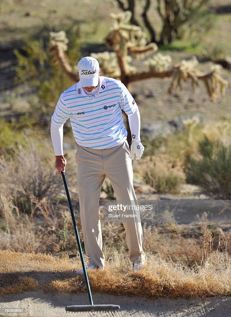 Steve Stricker rakes the sand in the bunker after he played a shot during the quarterfinal round of the World Golf Championships - Accenture Match Play at the Golf Club at Dove Mountain on February 23, 2013 in Marana, Arizona.