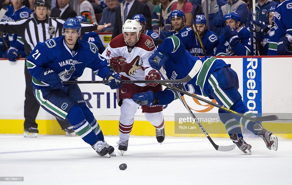 Steve Sullivan #26 of the Phoenix Coyotes tries to fight through the check of Mason Raymond #21 and Jordan Schroeder #45 of the Vancouver Canucks during the third period in NHL action on February 26, 2013 at Rogers Arena in Vancouver, British Columbia, Canada.