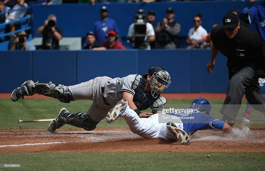 Steve Tolleson #18 of the Toronto Blue Jays slides across home plate to score the eventual winning run for the Blue Jays in the seventh inning during MLB game action as <a gi-track='captionPersonalityLinkClicked' href=/galleries/search?phrase=Francisco+Cervelli&family=editorial&specificpeople=4172506 ng-click='$event.stopPropagation()'>Francisco Cervelli</a> #29 of the New York Yankees reaches to make the tag on August 31, 2014 at Rogers Centre in Toronto, Ontario, Canada.