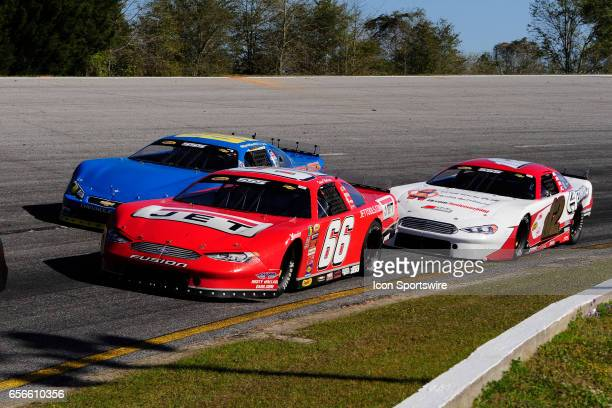 Steve Wallace Rusty Wallace Racing Ford Fusion leads Garrett Jones Chevrolet SS and Augie Grill Ford Fusion through turn two in the 41st Annual...
