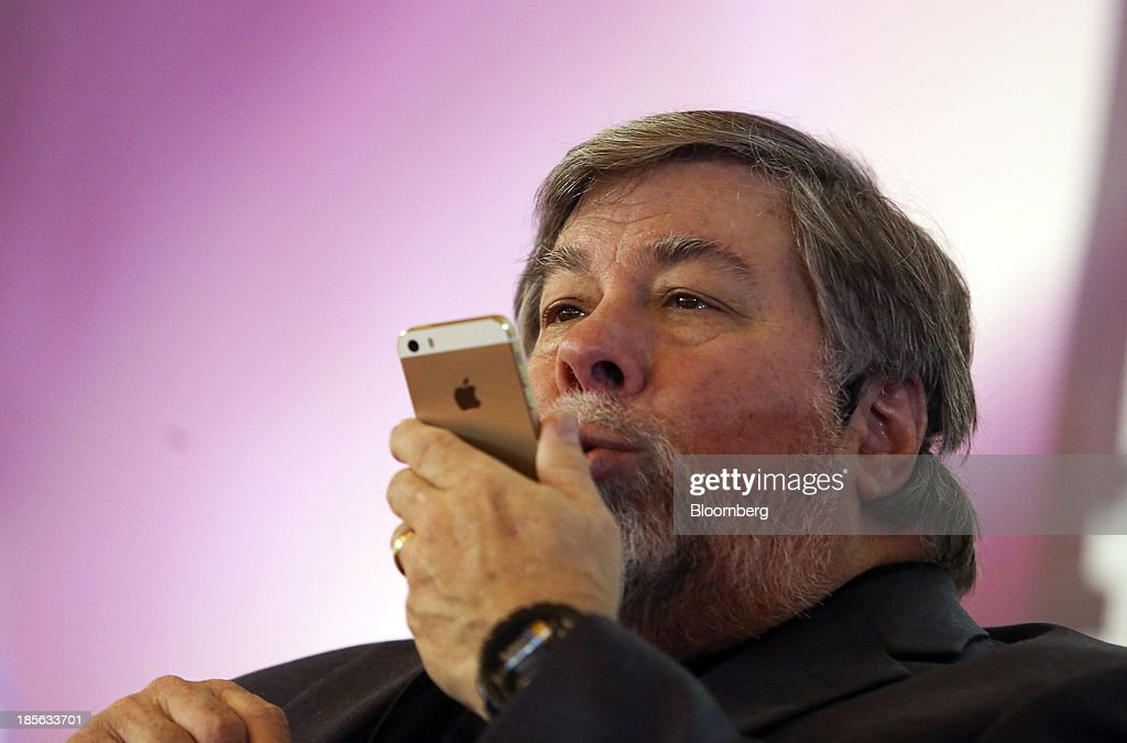 Steve Wozniak, co-founder of Apple Inc. and chief scientist of Fusion-io Inc., holds a gold Apple Inc. iPhone 5S smartphone as he speaks during the Apps World Multi-Platform Developer Show in London, U.K., on Wednesday, Oct. 23, 2013. Retail sales of Internet-connected wearable devices, including watches and eyeglasses, will reach $19 billion by 2018, compared with $1.4 billion this year, Juniper Research said in an Oct. 15 report. Photographer: Chris Ratcliffe/Bloomberg via Getty Images