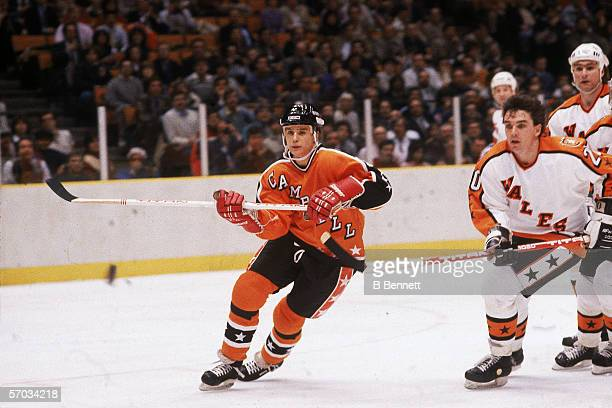 Steve Yzerman of the Campbell Conference and the Detroit Red Wings eyes the puck as he is pursued by Mike O'Connell and Ray Bourque of the Wales...