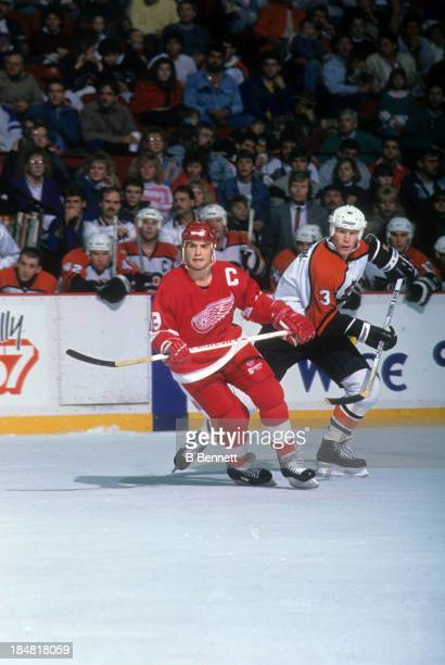 Steve Yzerman of the Detroit Red Wings skates on the ice as Gord Murphy of the Philadelphia Flyers follows behind on January 15 1989 at the Spectrum...