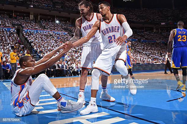 Steven Adams and Andre Roberson help up Kevin Durant of the Oklahoma City Thunder in Game Four of the Western Conference Finals against the Golden...