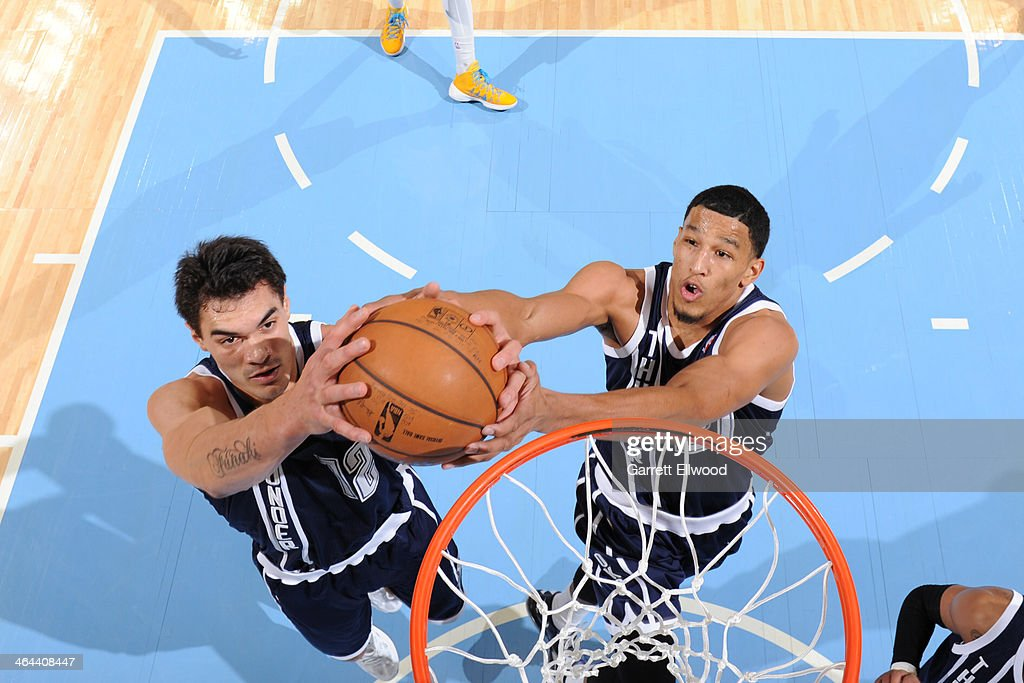 Steven Adams #12 and Andre Roberson #21 of the Oklahoma City Thunder grabbing a rebound during a game against the Denver Nuggets on January 9, 2014 at the Pepsi Center in Denver, Colorado.