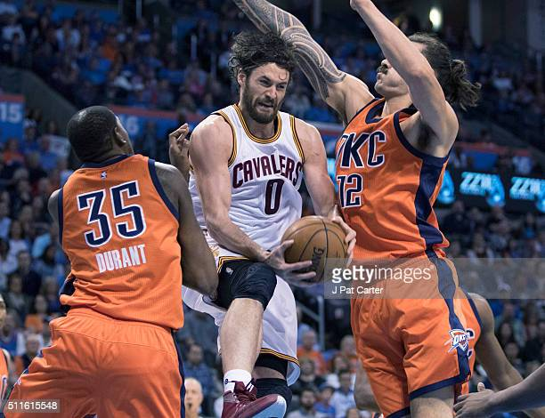 Steven Adams and Kevin Durant of the Oklahoma City Thunder try to block Kevin Love of the Cleveland Cavaliers as he looks for a shot during the first...
