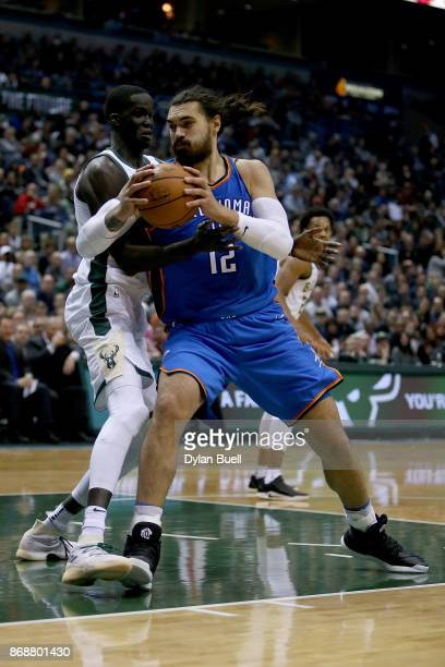 Steven Adams of the Oklahoma City Thunder dribbles the ball while being guarded by Thon Maker of the Milwaukee Bucks in the second quarter at Bradley...
