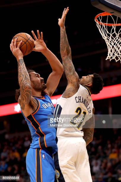 Steven Adams of the Oklahoma City Thunder drives to the basket against Wilson Chandler of the Denver Nuggets at the Pepsi Center on October 10 2017...