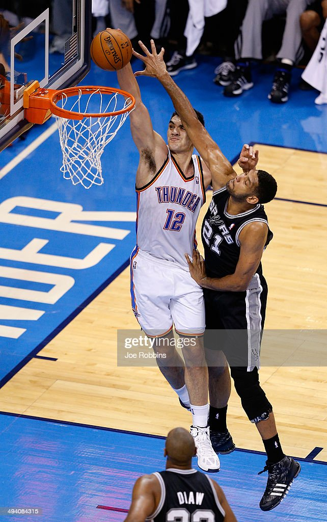 Steven Adams #12 of the Oklahoma City Thunder drives to the basket against <a gi-track='captionPersonalityLinkClicked' href=/galleries/search?phrase=Tim+Duncan&family=editorial&specificpeople=201467 ng-click='$event.stopPropagation()'>Tim Duncan</a> #21 of the San Antonio Spurs in the first half during Game Four of the Western Conference Finals of the 2014 NBA Playoffs at Chesapeake Energy Arena on May 27, 2014 in Oklahoma City, Oklahoma.