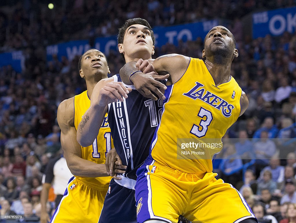 Steven Adams #12 of the Oklahoma City Thunder fights for position against Shawne Williams #3 of the Los Angeles Lakers at the Chesapeake Energy Arena on December 13, 2013 in Oklahoma City, Oklahoma.