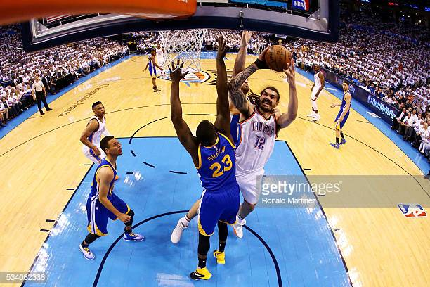 Steven Adams of the Oklahoma City Thunder goes up against Draymond Green and Andrew Bogut of the Golden State Warriors in the first half in game four...