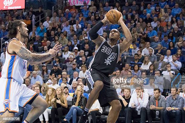 Steven Adams of the Oklahoma City Thunder tries to stop David West of the San Antonio Spurs from taking a shot during the fourth quarter of a NBA...
