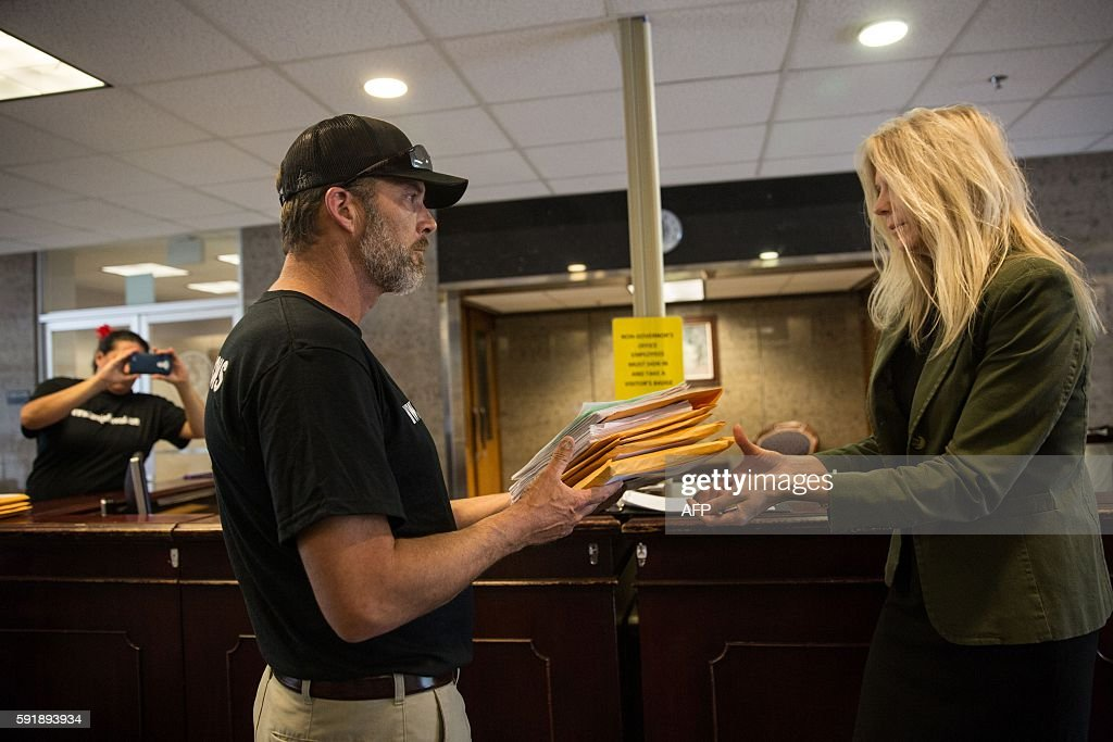 Steven Been brotherinlaw of Jeff Wood delivers a petition with over 10000 signatures to Johanna Hopkins a paralegal with the Office of General...