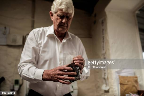 Steven Biggs owner of the Farm's lodge packages the coffee ground from his plantation on October 19 2017 in the British Overseas Territory of Saint...