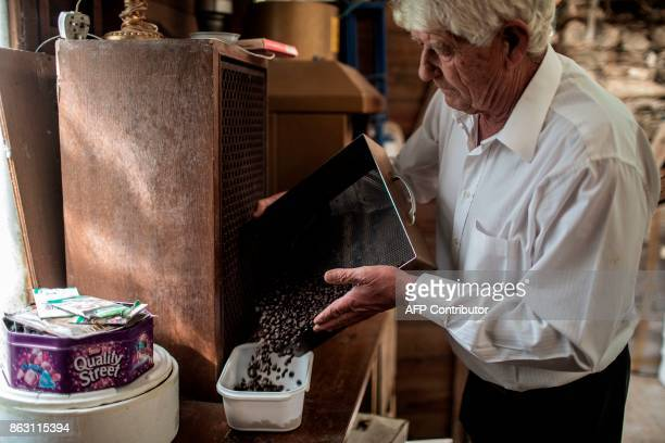 Steven Biggs owner of the Farm's lodge roasts coffee beans from his coffee plantation on October 19 2017 in the British Overseas Territory of Saint...