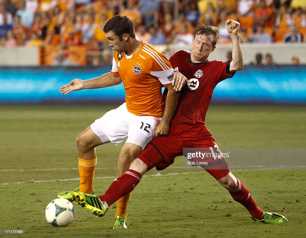 Steven Caldwell #13 of Toronto FC attempts to get the ball away from Will Bruin #12 of Houston Dynamo at BBVA Compass Stadium on June 22, 2013 in Houston, Texas.