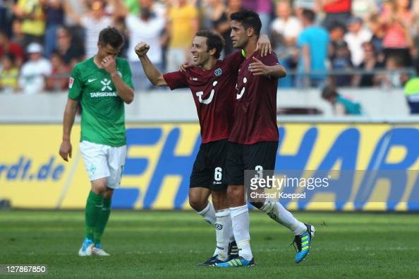 Steven Cherundolo and Karim Haggui of Hannover celebrate the 32 victory and Sebastian Proedl of Bremen looks dejected after the Bundesliga match...