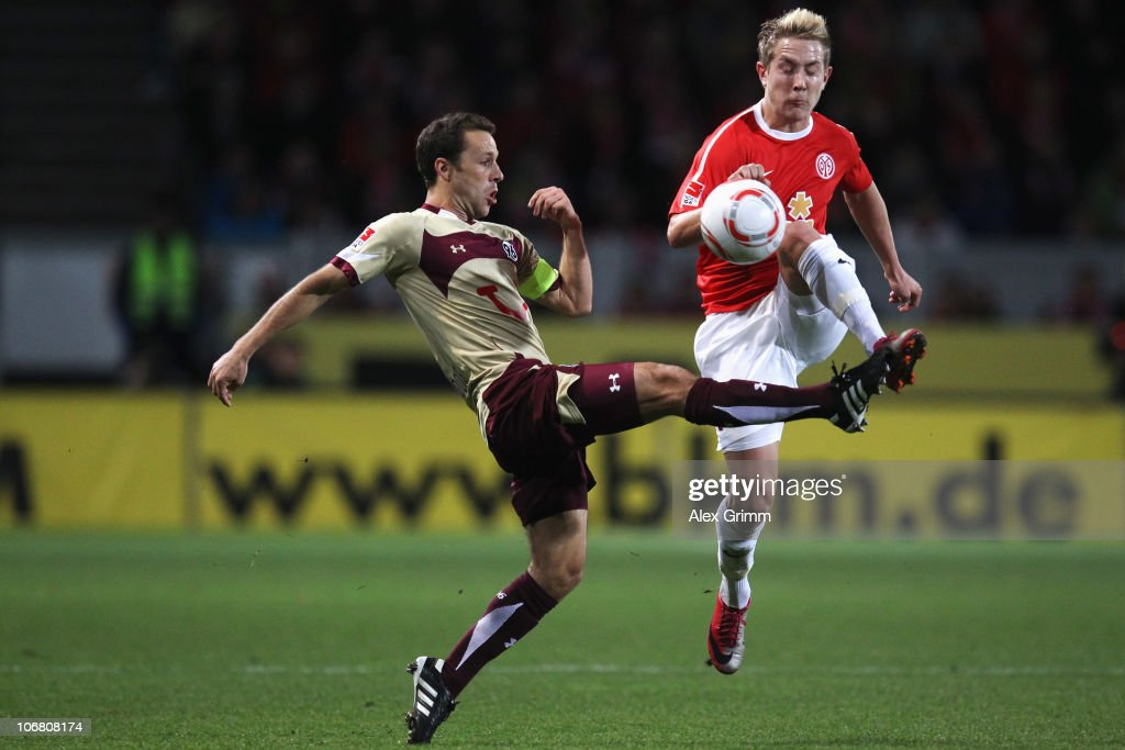 Steven Cherundolo of Hannover is challenged by Lewis Holtby of Mainz during the Bundesliga match between FSV Mainz 05 and Hannover 96 at the Bruchweg...