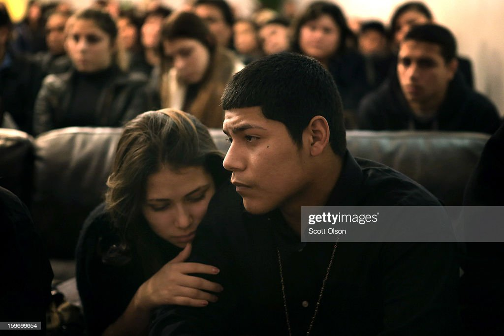 Steven Dorontes and his girlfriend Alexis Ramirez listen to a prayer at the wake of Steven's brother Rey January 17, 2013 in Chicago, Illinois. Fourteen-year-old Rey Dorantes died after being shot 6 times while he was sitting on the front porch of his home on January 11. Dorantes' murder was the 21st homicide recorded in Chicago for 2013, a city which saw more than 500 homicides in 2012.