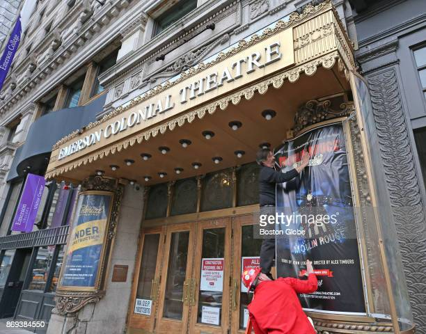 Steven Ehrenberg top and Justin Bolla install 'Moulin Rouge' artwork in a light box outside the Colonial Theatre in Boston on Nov 1 2017 The...