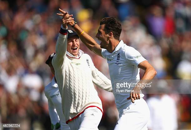 Steven Finn and Joe Root of England celebrate after taking the wicket of Adam Voges of Australia during day two of the 3rd Investec Ashes Test match...