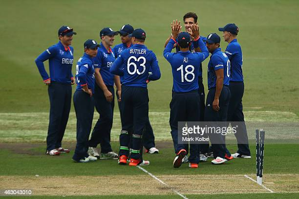 Steven Finn of England celebrates with his team mates after taking the wicket of Marlon Samuels of West Indies during the ICC Cricket World Cup warm...