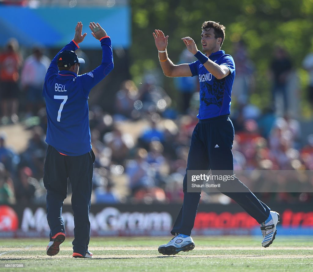 Steven Finn of England is congratulated by teammate Ian bell after taking a wicket during the 2015 ICC Cricket World Cup match between England and...