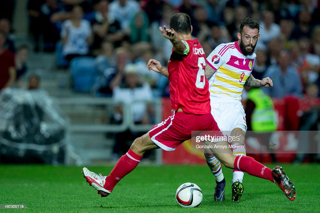 Steven Fletcher (R) of Scotland scores their fourth goal against Roy Chipolina (L) of Gibraltar during the UEFA EURO 2016 Qualifying round Group G match between Gibraltar and Scotland at Estadio Algarve on October 11, 2015 in Faro, Portugal.