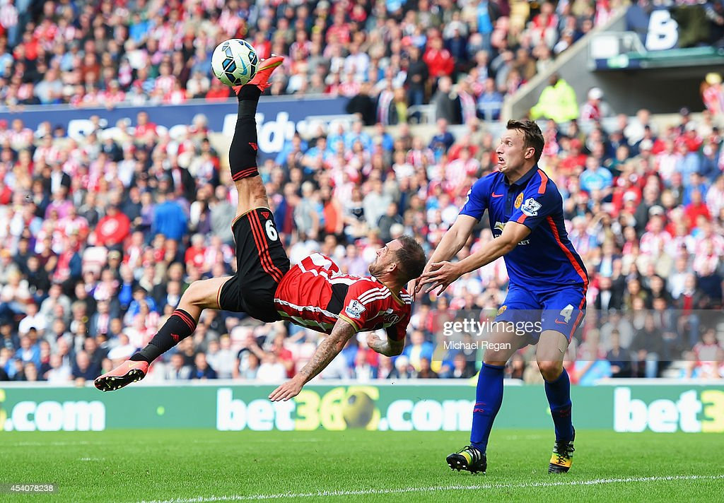 Steven Fletcher of Sunderland attempts an overhead kick with Phil Jones of Manchester United during the Barclays Premier League match between Sunderland and Manchester United at Stadium of Light on August 24, 2014 in Sunderland, England.