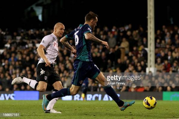 Steven Fletcher of Sunderland scores the opening goal as Philippe Senderos of Fulham closes in during the Barclays Premier League match between...